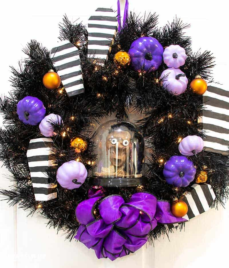 black wreath with purple punkims and black & white striped coffins on it with purple bow and shrunken Beetlejuice head inside