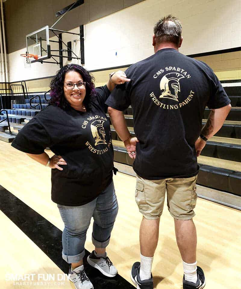 Couple wearing t-shirts customized with school logo for wrestling using Cricut