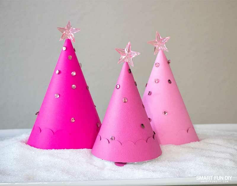 "3 pink paper Christmas Tree cones filled candies nestled on a platter covered with epson salt ""snow"""