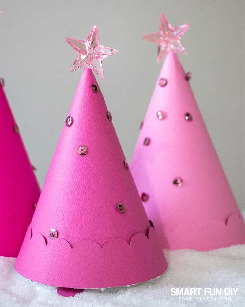 Pink paper cone Christmas trees decorated with sequins with gifts hidden inside