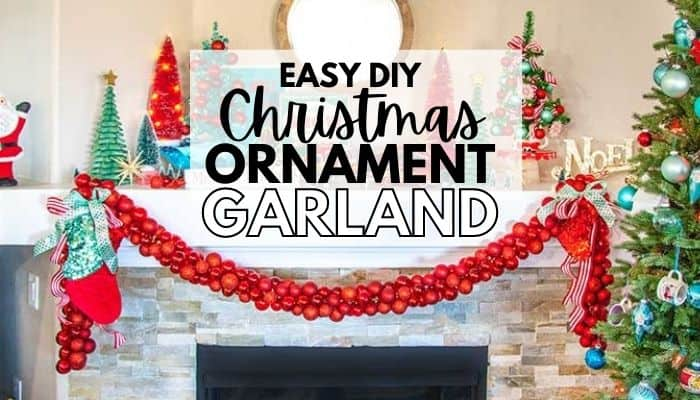 Fireplace mantle with red Christmas garland made from ball ornaments draped across the mantel and other vintage styles Christmas decorations on top of the mantel.