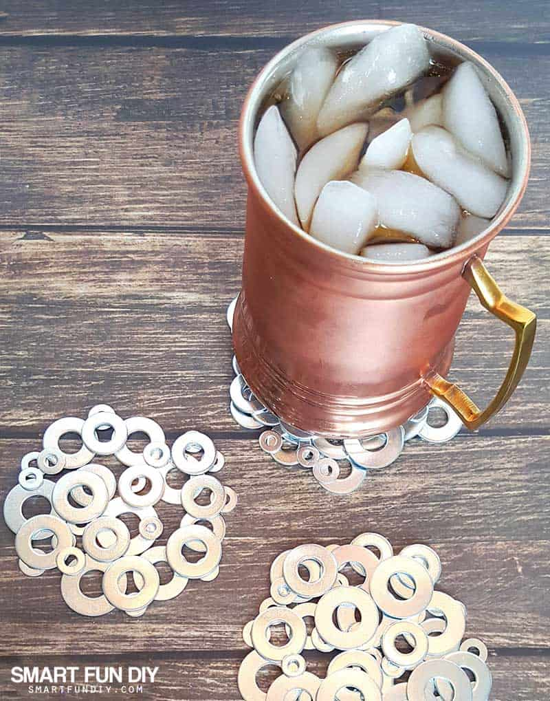 mug of soda with ice on top of plain metal washer coasters