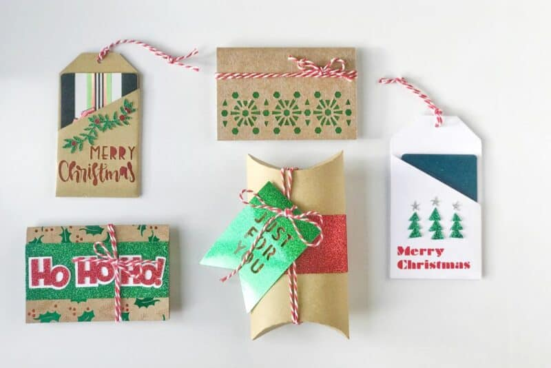 Assorted tags and pillow boxes for giving gift cards, created with Cricut digital cutting machine, in kraft paper, green glitter paper, red twine