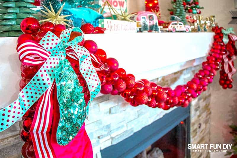 Fireplace mantle decorated for Christmas with chunky red ball ornament garland with bows tied at the corners