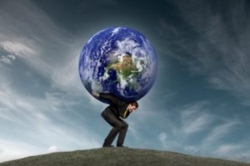 Conceptual royalty free stock image of a businessman carrying the world on his shoulders.