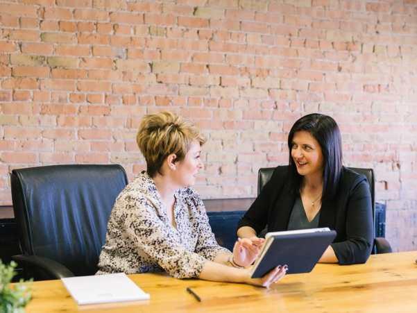 Empowerment two women talking office business meeting boardroom