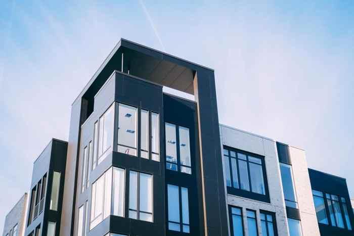 Apartment complex building construction silhouette glass blue sky houses