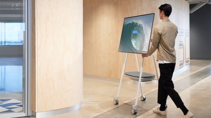 En mann flytter et stativ med en Microsoft Surface Hub 2S i kontorlokaler.