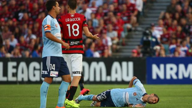 OUCH: Sydney FC star Ali Abbas lies on the Pirtek Stadium turf after suffering a season-ending injury in the tackle of Western Sydney Wanderers' Iacopo la Rocca.
