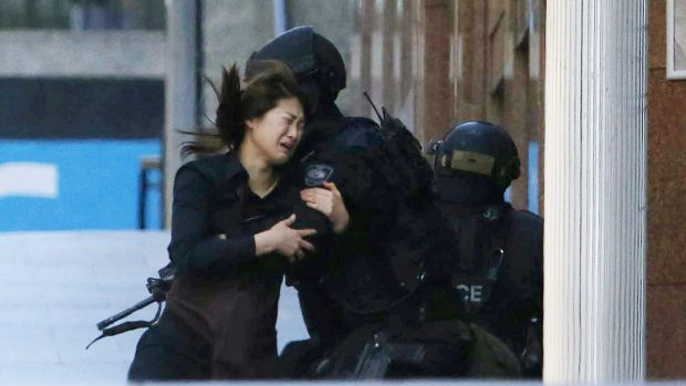 A hostage runs towards a police officer outside Lindt cafe.