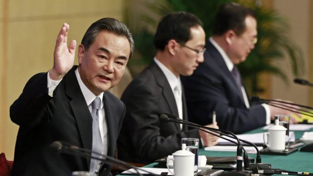 Chinese Foreign Minister Wang Yi  waves at a news conference at the annual session of the National People's Congress (NPC) in Beijing on Sunday.
