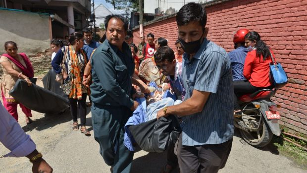 Nepalese patients are carried out of a Kathmandu hospital building as an earthquake hits the country on May 12.