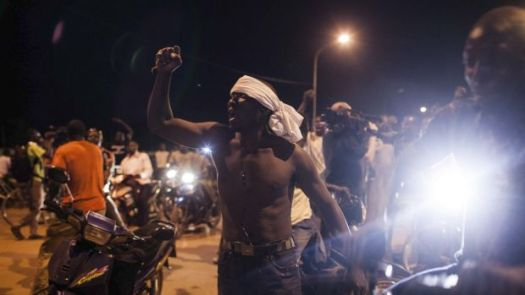 People demonstrate near the presidential palace after soldiers arrested Burkina Faso's leaders.