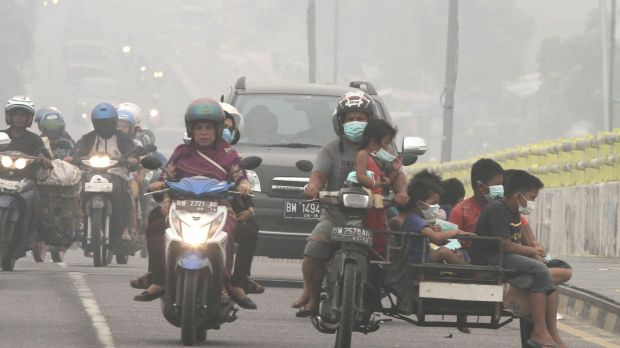 Motorists ride on a road as thick haze from wildfires blankets the city of Pekanbaru, Riau province, Indonesia, earlier this month.