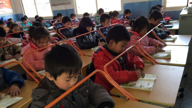 Chinese children read books with special desks equipped with iron bars to help them protect their eyesight.