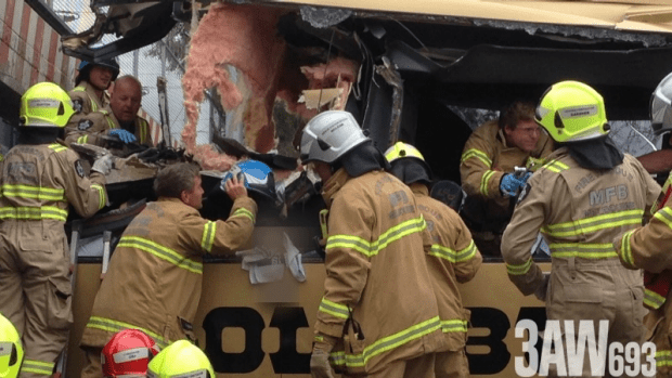 Firefighters working on the destroyed front of the bus.