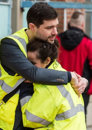 People comfort one another outside Brussels airport.