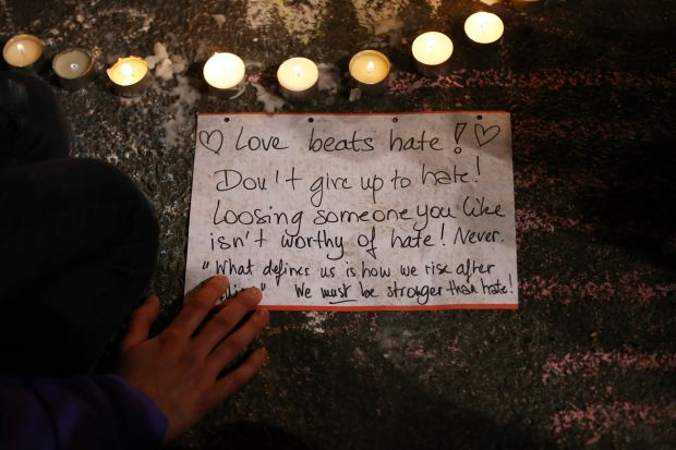 A person writes a message as people leave tributes at the Place de la Bourse following today's attacks.