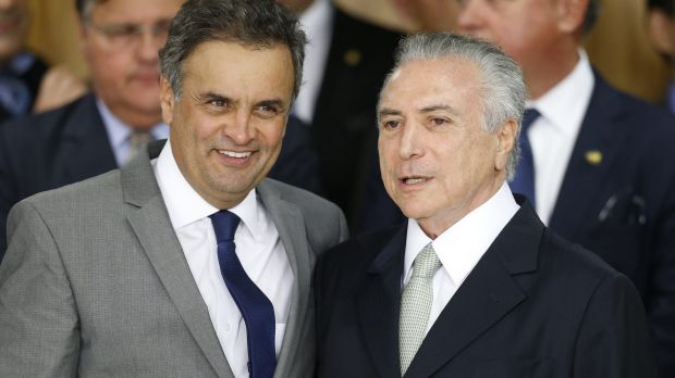 Brazil's interim President Michel Temer (right) hugs former presidential candidate Senator Aecio Neves at a signing ...