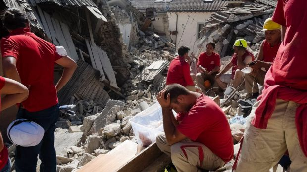 Rescuers pause as they work in Amatrice, central Italy, to find people who are trapped.