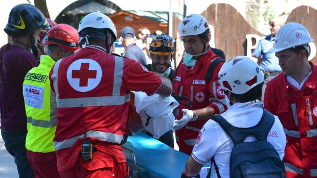 Rescue crews remove a body from a collapsed building at Amatrice.