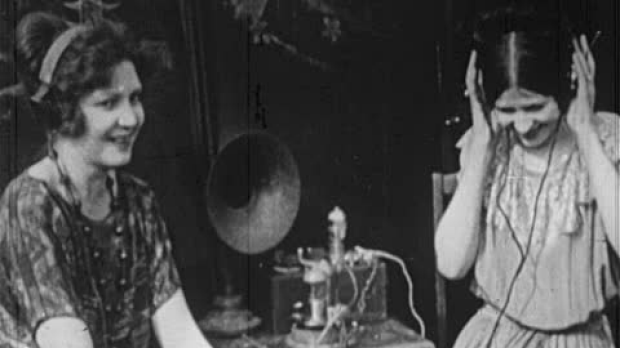 Two women listening to music through ancient pair of headphones in the 1920s.