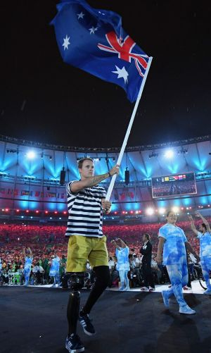 Gold medalist Curtis McGrath carries the flag for Australia during the closing ceremony of the 2016 Paralympic games in Rio.