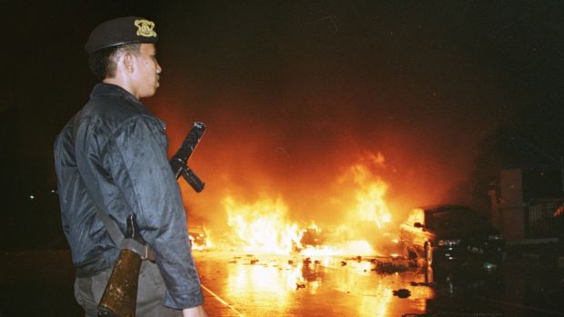 An Indonesian policeman, left, watches as cars burn in the street following a bomb explosion in front of a church in Jakarta Sunday night, Dec. 24, 2000. Religious tensions in mainly Muslim Indonesia flared Christmas Eve when a spate of bombs exploded outside the Roman Catholic Cathedral and other churches in Jakarta and other towns, killing some 10 people. (AP Photo/str)