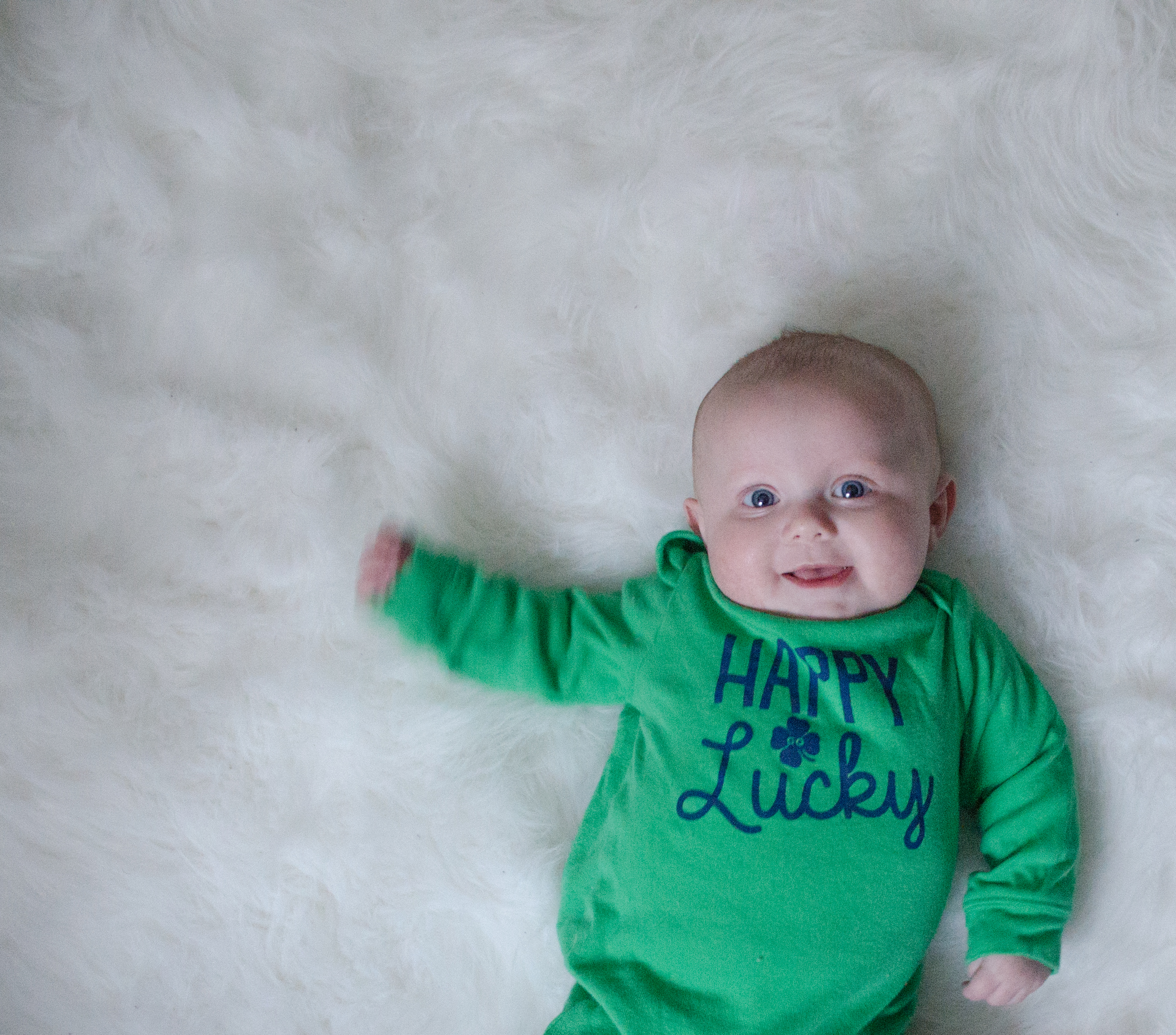 Baby in March St. Patrick's Day Onesie lying on faux-sheepskin rug.