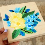 Painting acrylic flowers on a wood canvas