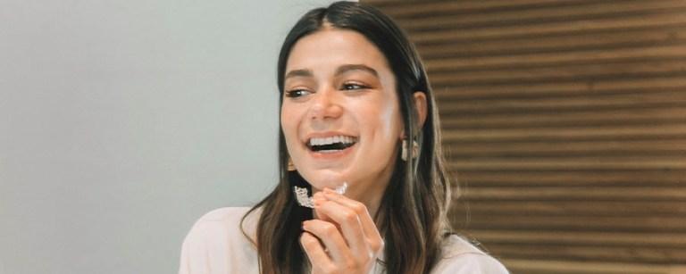 Mulher sorrindo e segurando o aparelho transparente