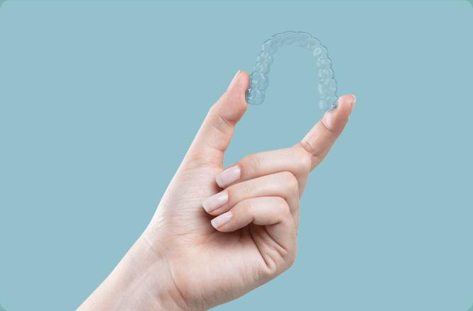 alinhar os dentes com alinhadores transparentes. Uma mão segurando um aparelho transparente sob um fundo azul claro