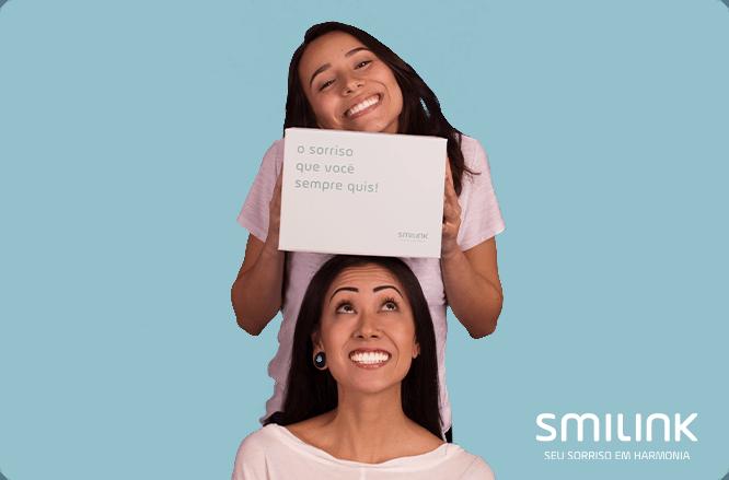 Alinhador invisível. Mulher segurando a caixa do kit ortodôntico personalizado de aparelho invisível sob a cabeça de outra mulher