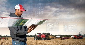 Soybean farming field tech standing in front of tractors with ipad