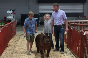 Rob Smith showng large pig with his kids