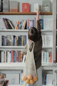 woman in beige long sleeve dress standing in front of white wooden book shelf