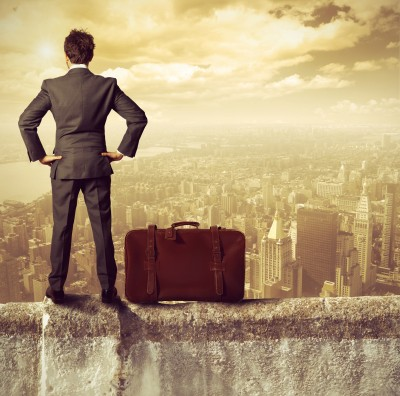 Businessman with suitcase looking over a golden, hazy city