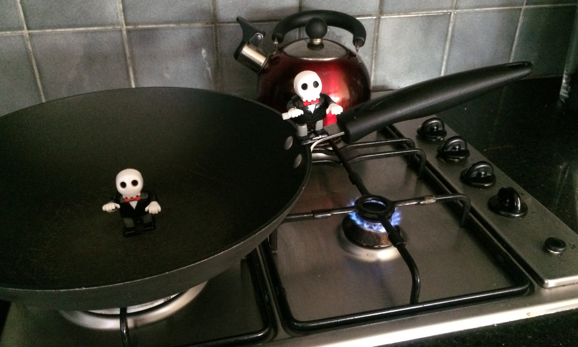 2 skeleton wind up toys jumping from wok to gas flame