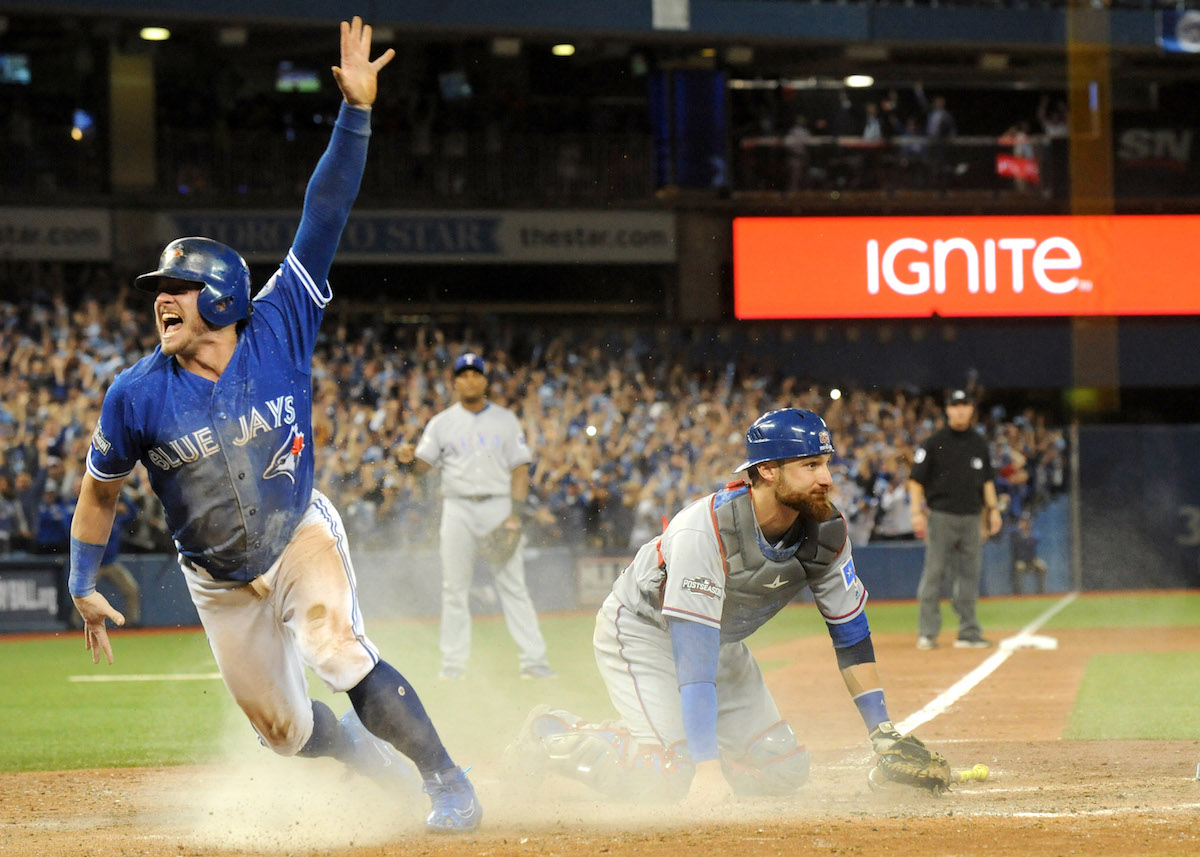 Oct 9, 2016; Toronto, Ontario, CAN;  Toronto Blue Jays third baseman Josh Donaldson (20) celebrates after scoring the winning run past Texas Rangers catcher Jonathan Lucroy (25) in the 10th inning to give the Jays a three game sweep in 2016 ALDS playoff series at Rogers Centre. Mandatory Credit: Dan Hamilton-USA TODAY Sports