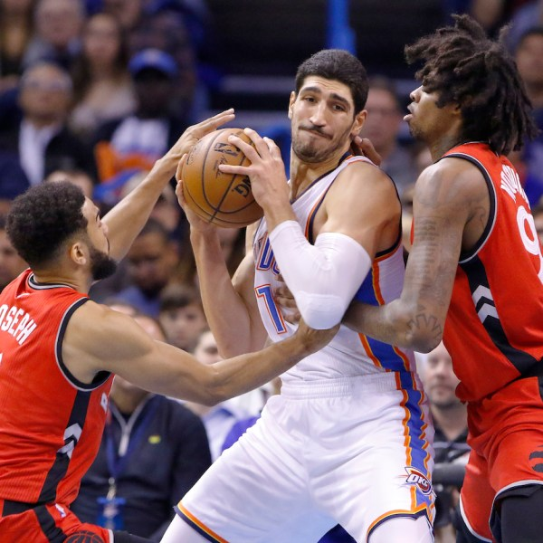 Oklahoma City Thunder center Enes Kanter, center, works to keep the ball away from Toronto Raptors guard Cory Joseph, left, and center Lucas Nogueira, right, during the first half of an NBA basketball game in Oklahoma City, Wednesday, Nov. 9, 2016. (AP Photo/Alonzo Adams)