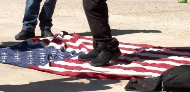 Does This Photograph Show a Migrant Caravan Member Urinating on the U.S.  Flag?
