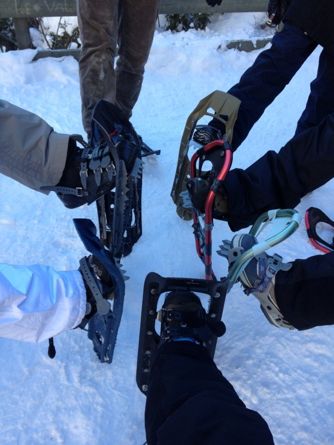 people lifting their leg to hold up their snowshoes