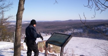 man observing info sign at Ice Age Trail with view overlooking a frozen lake