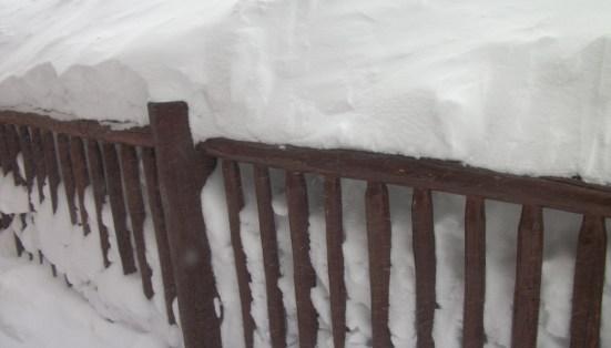Breckenridge hut railing with multiple feet of snow