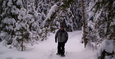 senior snowshoeing alone and surrounded by trees