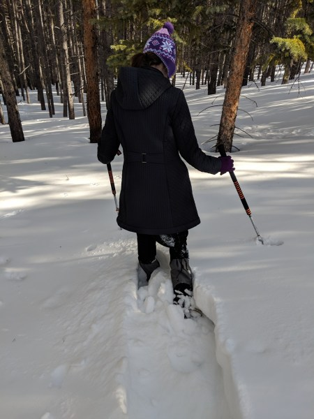 snowshoeing tips for choosing snowshoes: woman in snow sinking to knees on snowshoes
