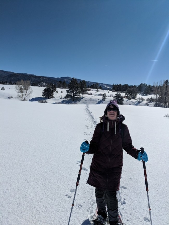 snowshoeing clothing: woman snowshoeing in freshly fallen snow in Chama, NM