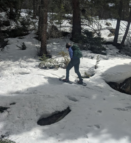 woman snowshoeing with MSR Lightning Ascents up a hill