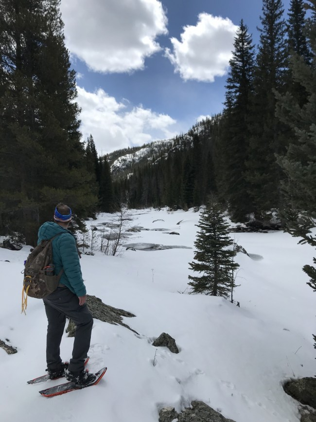 man with snowshoes looking at river