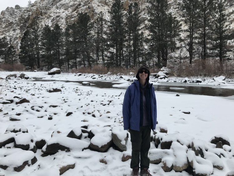 woman standing in snow near river and rocks